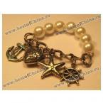 Стильный браслет, украшенный искусственными жемчугами и различными подвесками.